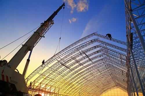 工人利用晴好天气进行钢结构吊装